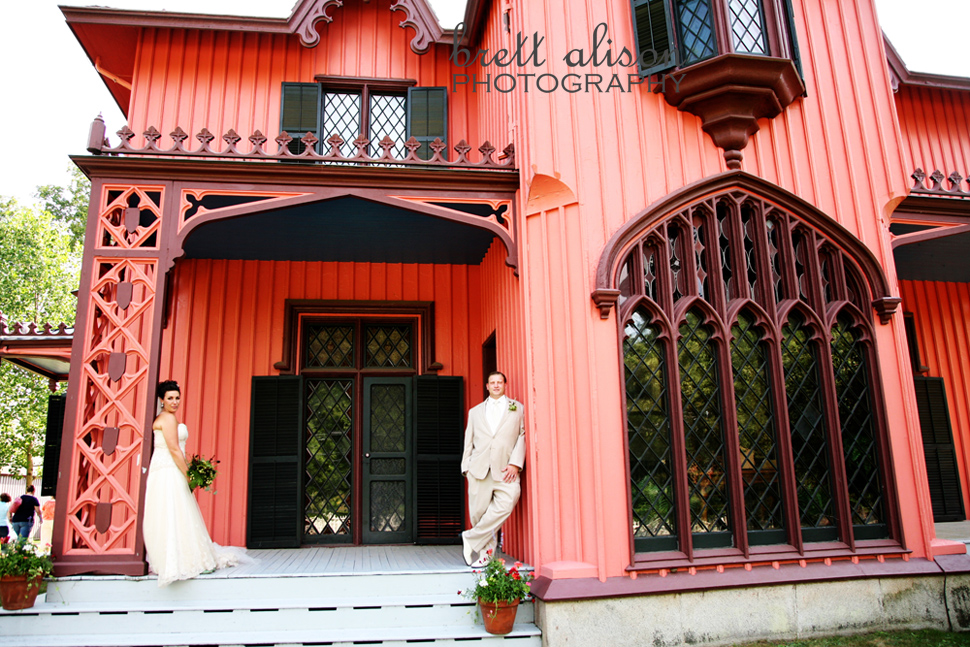 bride and groom in front of red roseland cottage